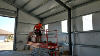 Project 2. One of our technicians using some equipment to put in high bay lights.